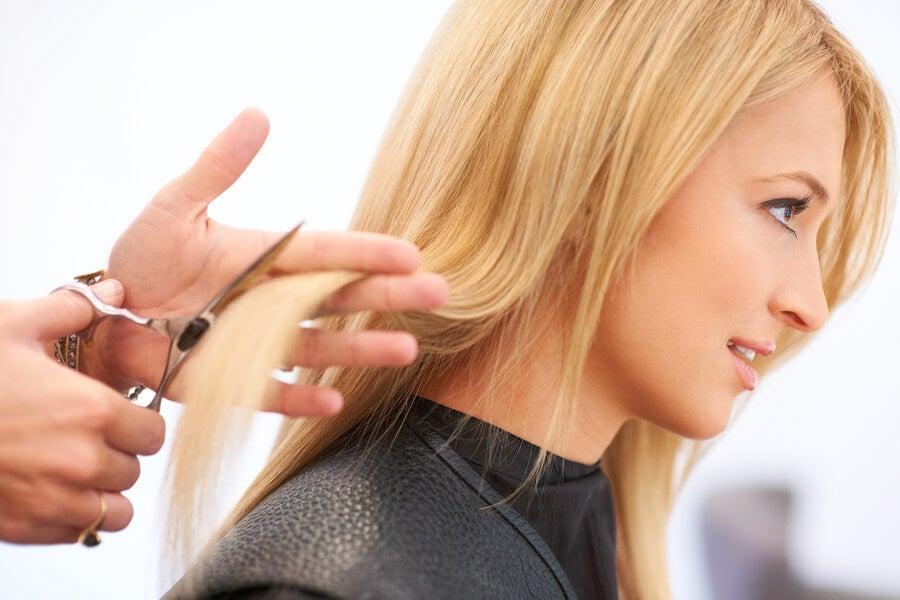 Fryzjer podcina kobiecie włosy