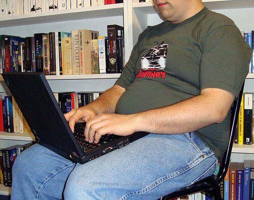 Otyły mężczyzna przy laptopie