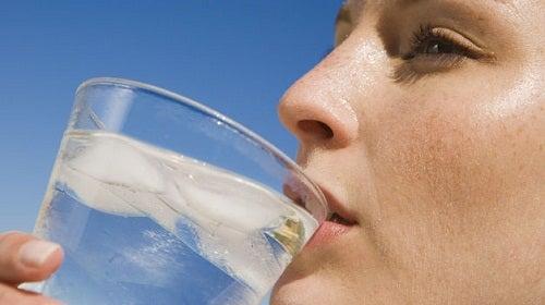 Kobieta pijąca wodę z lodem