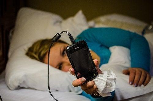 Kobieta w łóżku z telefonem w ręku