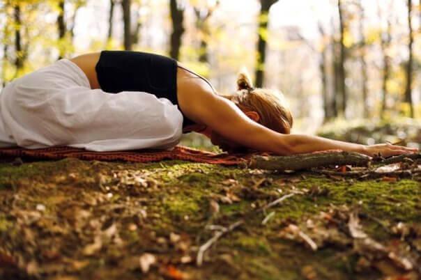 Kobieta ćwiczy jogę w lesie