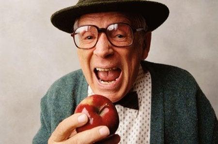 Starszy mężczyzna je jabłko