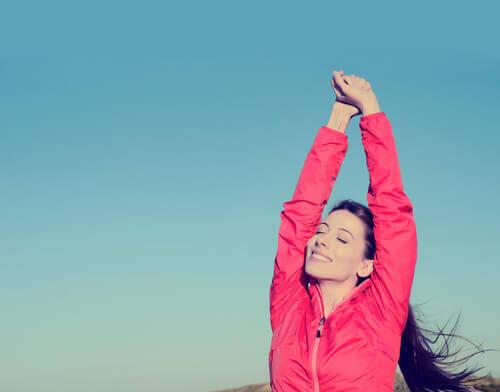 Zadowolona kobieta wyciąga ręce do góry
