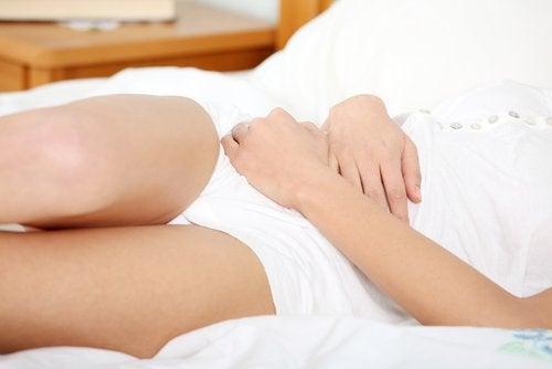 Kobieta trzymająca się za brzuch