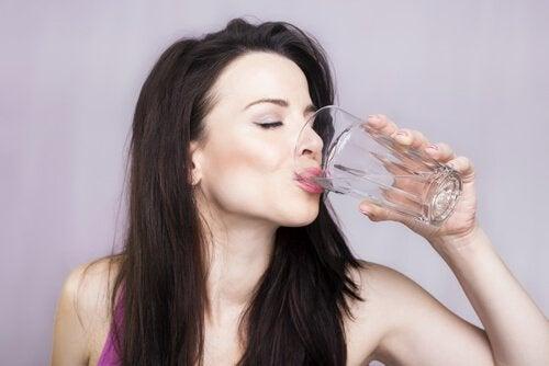 Kobieta pije wodę, by mieć zdrowe nerki