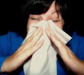 zapalenie zatok przynosowych - kobieta wycierająca nos chusteczką