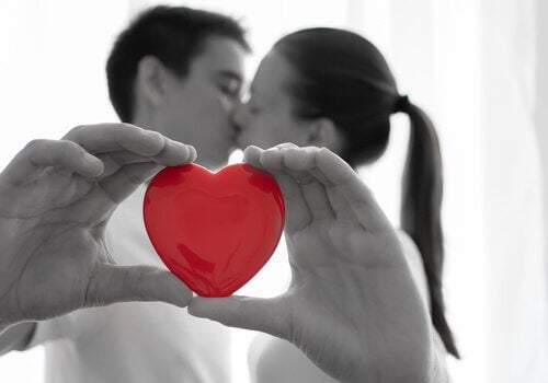 Całująca się para i czerwone serce