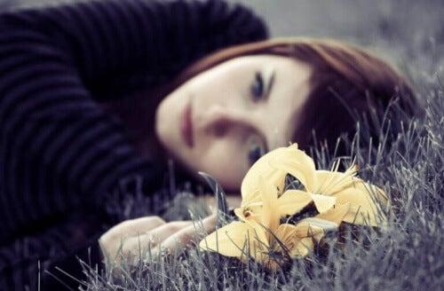 Smutna kobieta leży na łące