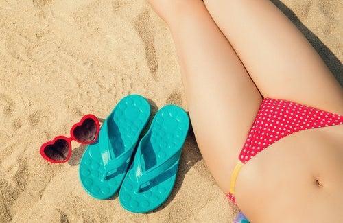 ciało na plaży obok klapków i okularów