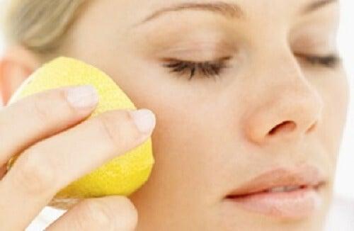 Kobieta trzyma przy twarzy cytrynę