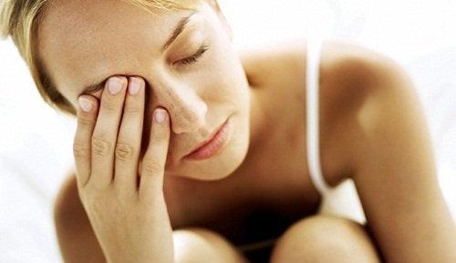 Zmęczona kobieta zakrywa ręką twarz