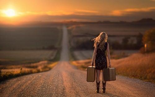 Dziewczyna idzie z walizkami drogą