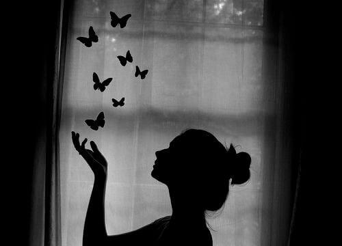 Kobieta wypuszczająca z dłoni motyle