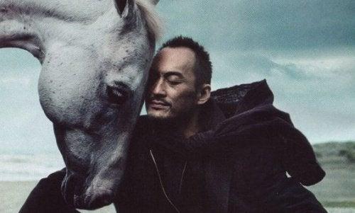 Człowiek przytulony do konia