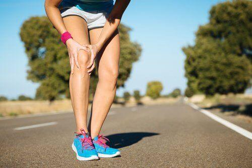 Biegaczka schyla się z powodu bólu kolana