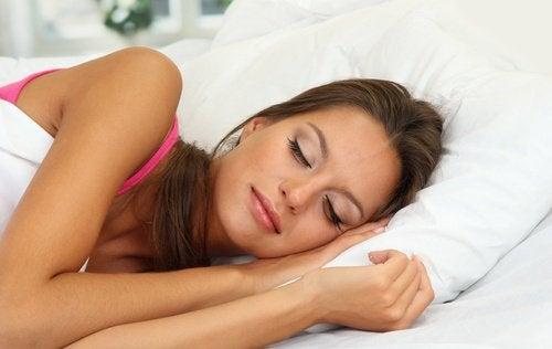 Kobieta śpiąca w łóżku.
