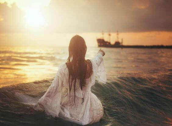 Kobieta siedząć na brzegu wskazuje statek