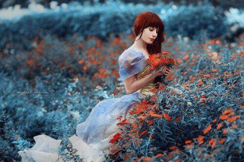Zamyślona kobieta w polu czerwonych kwiatów