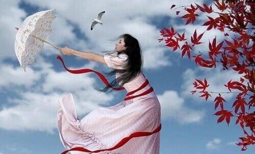 Kobieta z parasolem na wietrze.