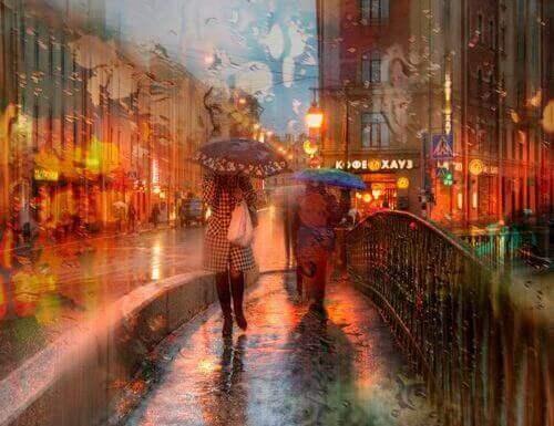 Kobiety z parasolkami przechodzą przez most w deszczu