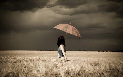 Kobieta z parasolem w polu.