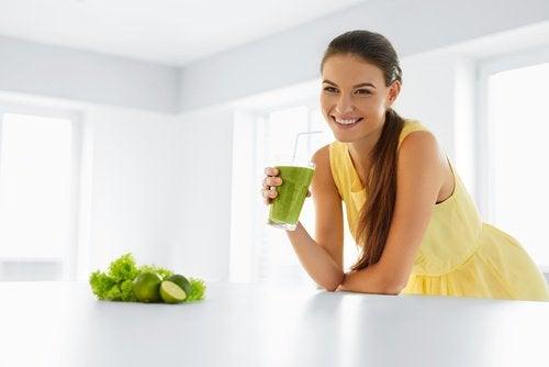 Kobieta trzyma w ręce zielony, relaksujący koktajl