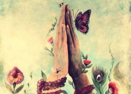 Złożone ręce wśród motyli i kwiatów