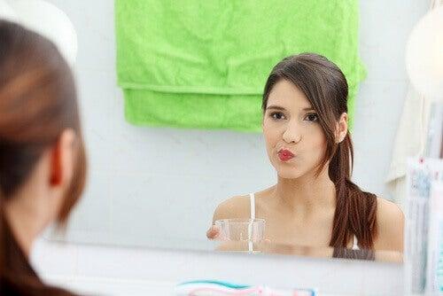 kobieta płucząca usta płynem na wrzody w jamie ustnej