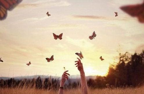 Dłonie dosięgające motyli