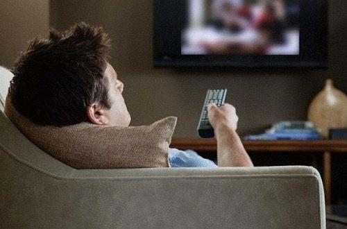 Mężczyzna w fotelu ogląda telewizję w pozycji wywołującej ból szyi