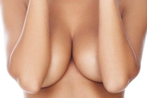 Ręce zakrywające nagie piersi - zalety chodzenia bez biustonosza