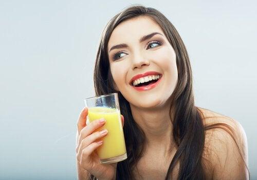 Kobieta trzyma szklankę wody ananasowej
