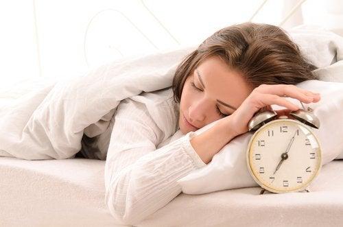 Śpiąca kobieta z ręką na budziku