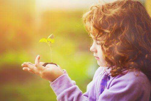 dziecko z rosnącą roślinką na dłoni