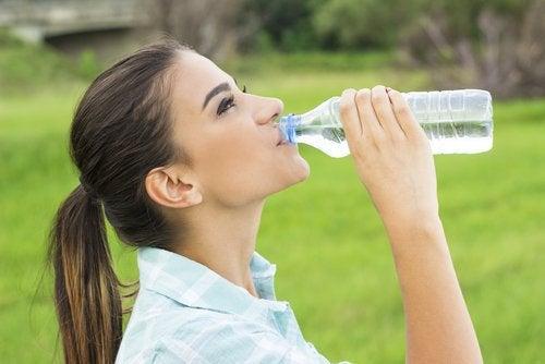 Kobieta pije wodę, by zwalczyć kamienie nerkowe