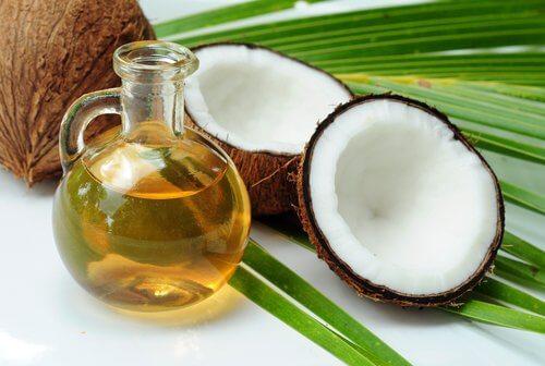 Naturalny olej kokosowy w dzbanuszku i orzechy kokosowe na liściach palmy - młodszy wygląd