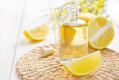 kawałki cytryny i butelka olejku cytrynowego