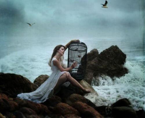 Kobieta z klatką na brzegu morza