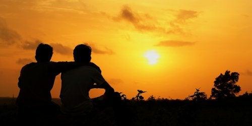 Przyjaciel obejmuje przyjaciela o zachodzie słońca