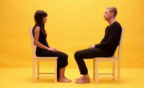 Dwie osoby siedzą na krześle naprzeciw siebie
