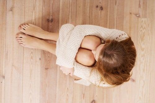 Skulona kobieta siedzi na podłodze
