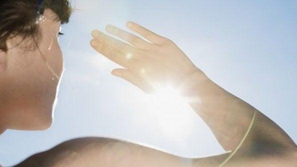 Kobieta zakrywa ręką twarz przed słońcem