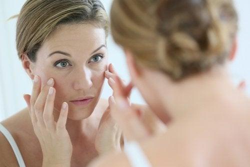 kobieta smaruje kremem oczy