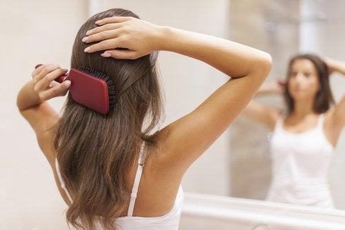 kobieta szczotkuje włosy przed lustrem