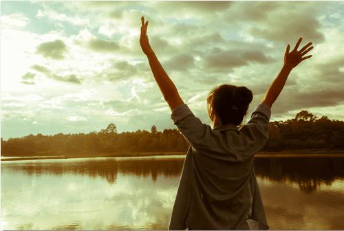 kobieta nad jeziorem unosi ręce