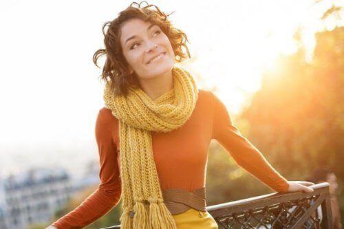 uśmiechnięta kobieta oparta o balustradę