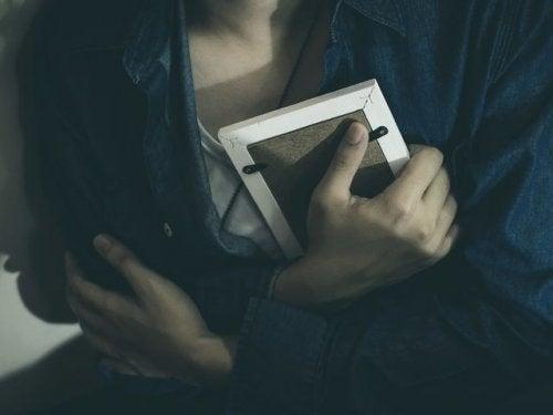 Kobieta ściska ramkę ze zdjęciem - wspomnienia