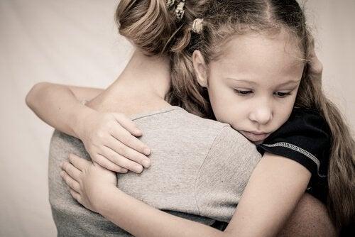dziewczynka przytulona do matki