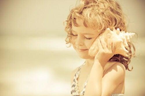 dziecko przykłada muszlę do ucha