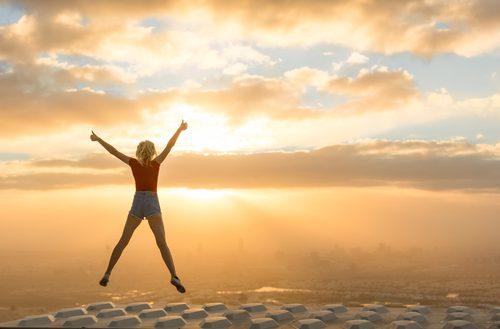 Kobieta skacze o zachodzie słońca